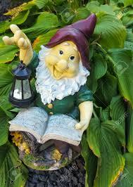 garden gnome with lantern reading a book stock photo 23294419