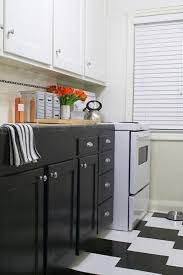 Two Tone Kitchen With White Upper Cabinets And Dark Lower Cabinets And Black  U0026 White Checkered Tiles Floor.