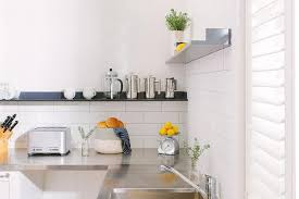 white kitchen with stainless steel countertops and black shelf