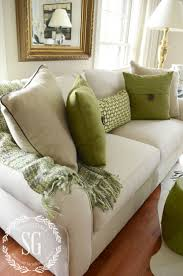 neutral and green pillows on a neutral sofa with a green throw