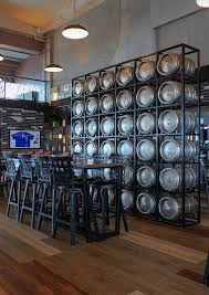 at the center of the bar there is a wall made out of beer kegs