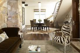 living room ideas with cowhide rug. beautiful cow hide rug under dining furniture and crystal chandelier for traditional family room with staircase living ideas cowhide
