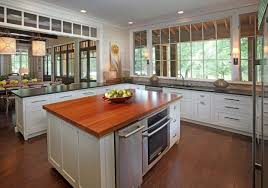 White Laminated Wooden Kitchen Island With Brown Laminated Wooden Countertop  And Silver Microwave On Brown Laminated Wooden Floor White Wall With White  ...