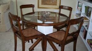 round glass dining table with brown wooden frame and white wooden
