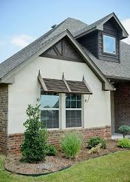 cream stucco Beacon Homes: Hawkins Point floor plan with Bermuda shutter,  ivory buff stucco, and brick wainscoting