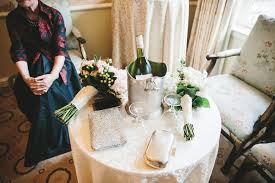 a doentary photograph of a grandmother sitting by a table with wedding bouquets hand bags