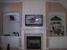 white fireplace under wall mount tv among white stained wooden built in display rack