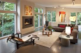 in this living room holding modern armless brown sofa with red and cow pattern pillows white rug at center olds wood and glass coffee table