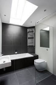 the large black stone tiles in this bathroom help to create a simple black and white color scheme and the light from the skylight makes the bathroom feel