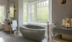 bathroom features gray shaker vanity: incredible bathroom features a windowed alcove which highlights a gray oval freestanding tub with modern tub filler flanked by a pair of floating veneer