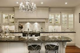 this beautiful crystal chandelier fits in this kitchen design perfectly the chandelier combined with other decorative elements adds a luxury vibe to this