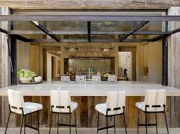 patio kitchen pass through boasts reclaimed wood plank walls framing an outdoor bar lined with iron barstools with striped cushions under a metal and glass