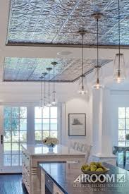 A hand-stamped tin ceiling defines the dual islands in this Nantucket style  kitchen in