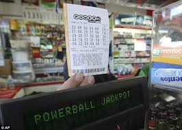 national lottery players furious as £57m jackpot goes unclaimed excitement in the us a shop employee holds a powerball lottery ticket in richmond
