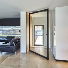 custom made glass pivot door between entrance and living area