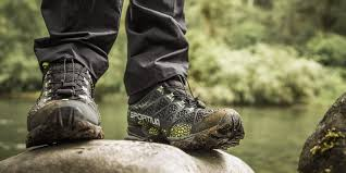 a hiker wearing a pair of muddy boots along the trail