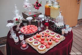 wedding candy bar buffet on the table with a tablecloth color marsala are