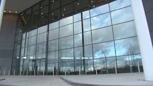 glass exterior modern office. time lapse exterior of modern office building clouds and business people rush by in this glass r