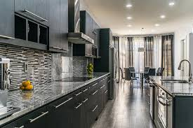 modern kitchen with tile backsplash and dark cabinets topped with super white marble countertops and stainless