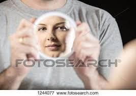Picture of Man holding hand mirror showing reflection of beautiful