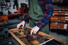 crop of young craftsman looking through tray of wooden letterpress letters in print work