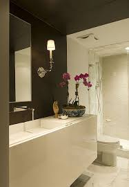Glossy white lacquer modern floating bathroom vanity, chocolate brown walls,  modern faucet, sconces, marble tiled floors and frameless glass shower.