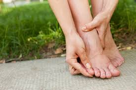 a woman with foot pain perhaps with corns and calluses rubbing her toes