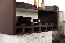 dark espresso wooden wall mounted wine rack with glass holder underneath plus top shelf hanging on white wall theme