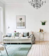 living room white walls floor boards and couch light light blue rug living room