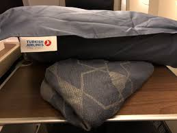 at first i thought wow this is really bad bedding the blanket provided on the seat was nothing more than an economy class blanket