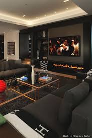 An awesome man cave with comfortable, dark furniture, glass coffee tables  and an electric