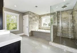 bathroom with glass frameless shower with travertine tile and rain showerhead