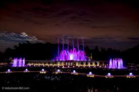 night fountain show with water fountains lit in pink purple as they move to