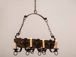 old and vintage wood and black iron chandelier with candle holder and hanging with chains for rustic dining room or kitchen lighting ideas