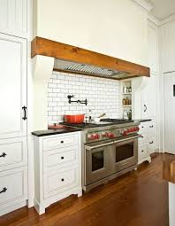 gorgeous kitchen features walls clad in beadboard trim framing a large kitchen hood with wood trim which is suspended over a subway tiled backsplash with