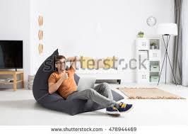 modern bean bag furniture. young man sitting on a modern bean bag drinking coffee watching something his furniture