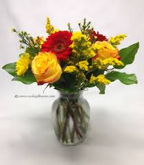 fall flowers 006 45 plus tax and delivery fall flower arrangement with yellow roses and red gerber daisies and yellow soli in clear gl tulip