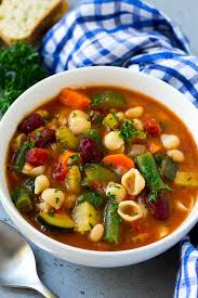 a bowl of olive garden minestrone soup full of pasta green beans vegetables and