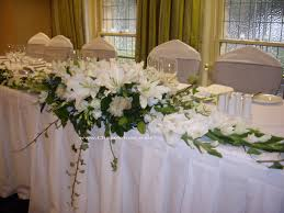 Interior. large table with white tablecloth combined by white flower  bouquet with green leaves also