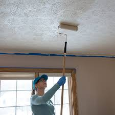 Woman rolling paint onto the ceiling
