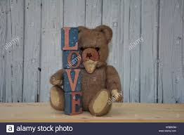 old antique teddy bear with love lettering against white wooden wall on vintage teddy bear wall art with old antique teddy bear with love lettering against white wooden wall