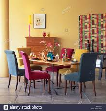 pink turquoise and blue velour upholstered dining chairs at table in modern yellow dining room with multi colored screen