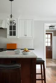 The glass cabinets in this kitchen have clear seedy glass with wood mullions and the interior lighting displays the homeowner's dishware and accent pieces. White Kitchen With Cherry Island Design Ideas