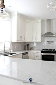 low contrast white kitchen with bianco drift quartz countertops and gray subway tile backsplash kylie