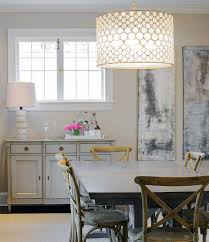 chic dining room features an oly studio serena drum chandelier hanging over a rectangular dining table lined with french x back dining chairs