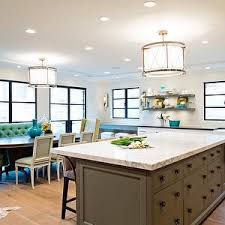 center island lighting. open plan kitchen boasts nickel and glass drum pendant light illuminating taupe island fitted with paneled dishwasher topped white marble center lighting