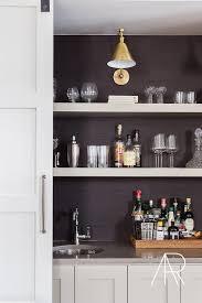 alyssa rosenheck bar with sliding door and floating shelves lining a black grasscloth backsplash
