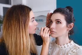 a make up artist holds a model s head with one hand and applies eyeliner with