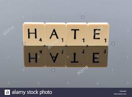 Scrabble Letters Spelling Out The Word Hate With Reflection