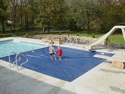 automatic pool covers. Two Children Or Kids Standing On A Half Closed Pool Cover. These Covers Are Automatic O